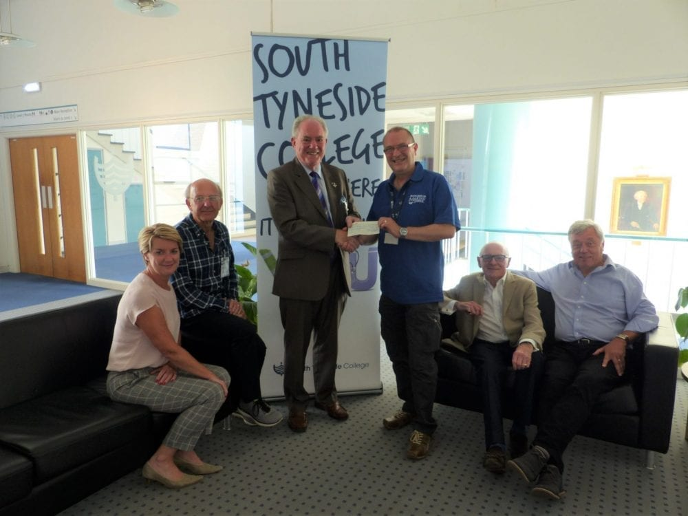 John Lightfoot, MBE, chairman of Solar Solve Marine, hands over a donation from his company to William Craik, Senior Technician at South Tyneside College and a member of the Dr. Winterbottom Charitable Fund committee, watched by four of the other committee members.
